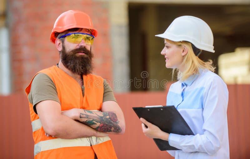 妇女审查员和有胡子的残酷建造者谈论建筑进展 工程项目检查 建筑 免版税库存图片