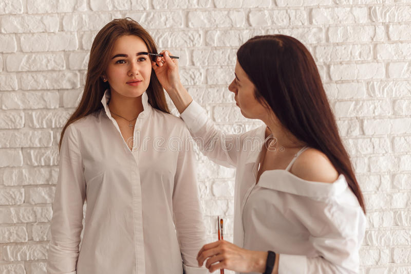 妇女客户和美容师完成眼眉的更正 免版税库存图片