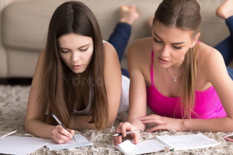 妇女家庭教师在家与十几岁的女孩衔接 图库摄影