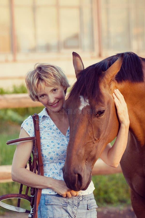 妇女容忍褐色马 库存图片