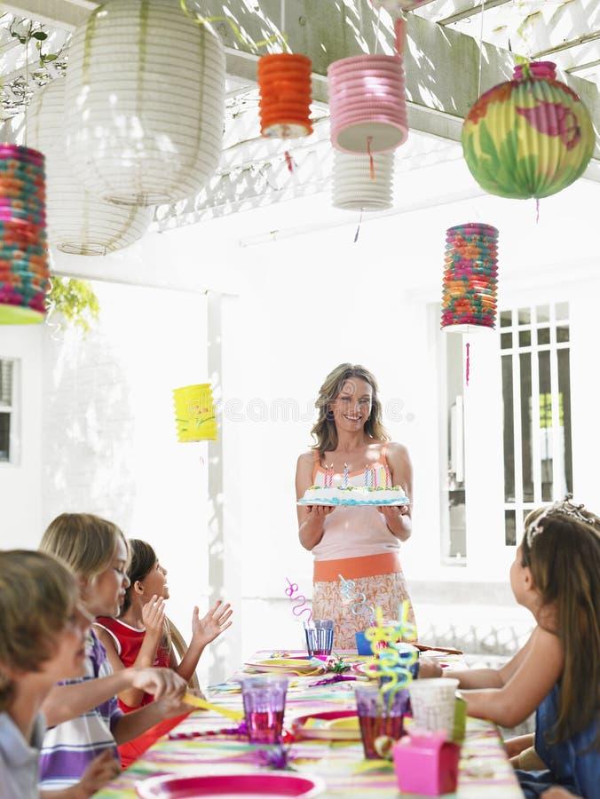 妇女对孩子的服务蛋糕生日聚会的 图库摄影