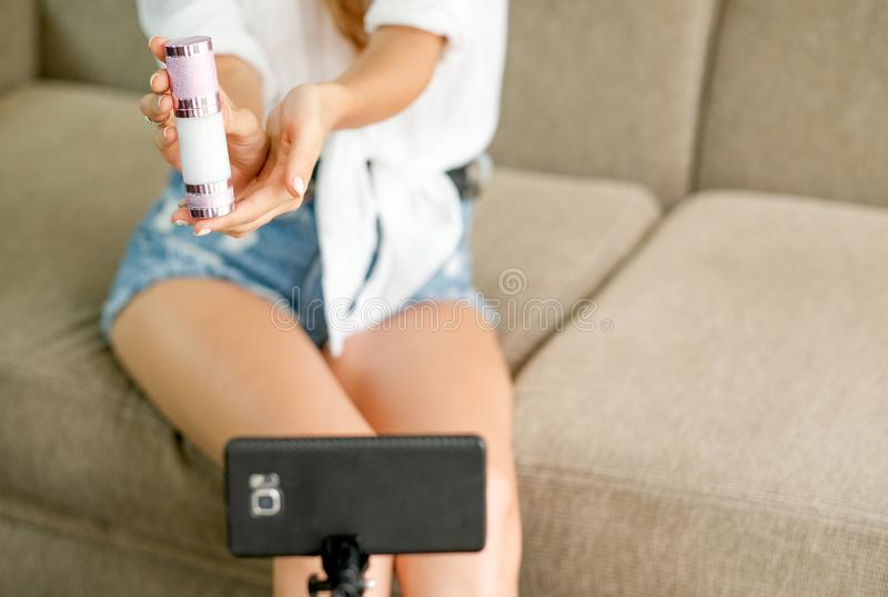 妇女对手机照相机的展示化妆品有直播的概念的网络购物的 免版税库存照片