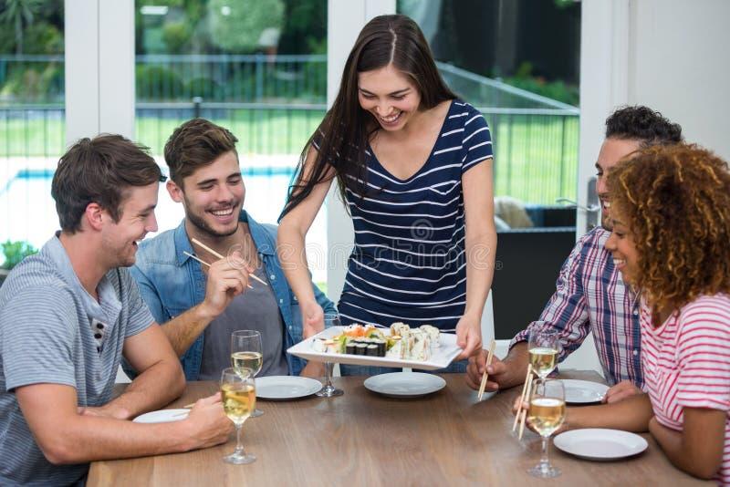 妇女对朋友的服务寿司,当喝酒时 库存照片