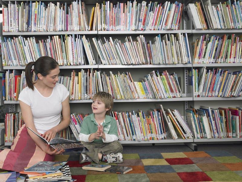 妇女对男孩的阅读书在图书馆里 库存照片