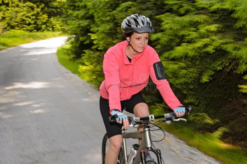 妇女山骑自行车的行动迷离循环的道路 免版税库存图片