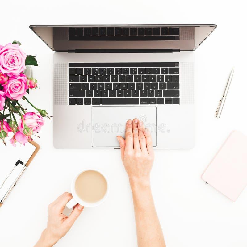 妇女工作区用女性手,膝上型计算机,桃红色玫瑰花束,咖啡杯,日志 顶视图 平的位置家庭办公室书桌 女孩workin 免版税库存照片