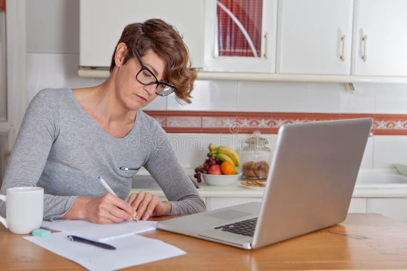 妇女工作或blogging在家庭办公室 免版税库存照片