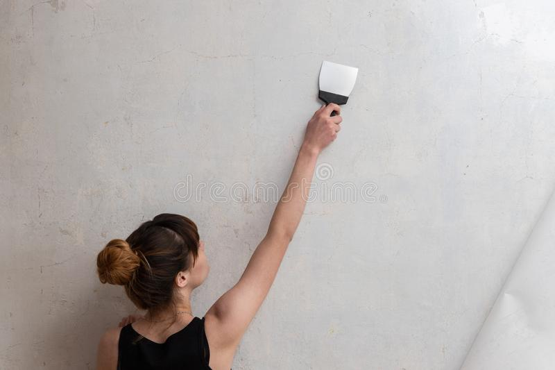妇女带领在一个混凝土墙上的一把小铲 公寓的整修 免版税库存图片