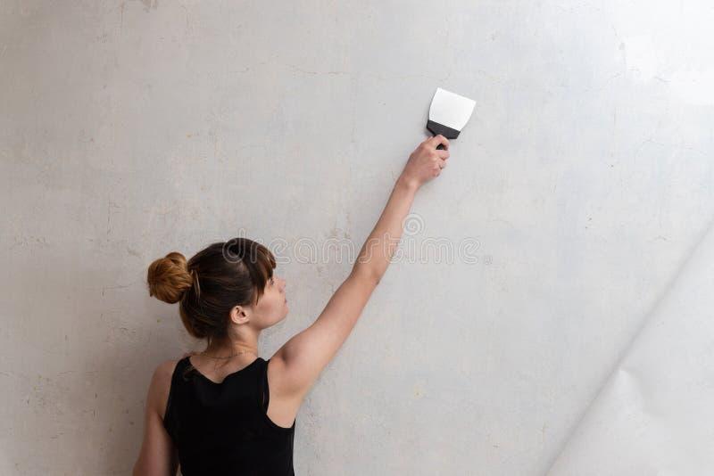 妇女带领在一个混凝土墙上的一把小铲 库存照片