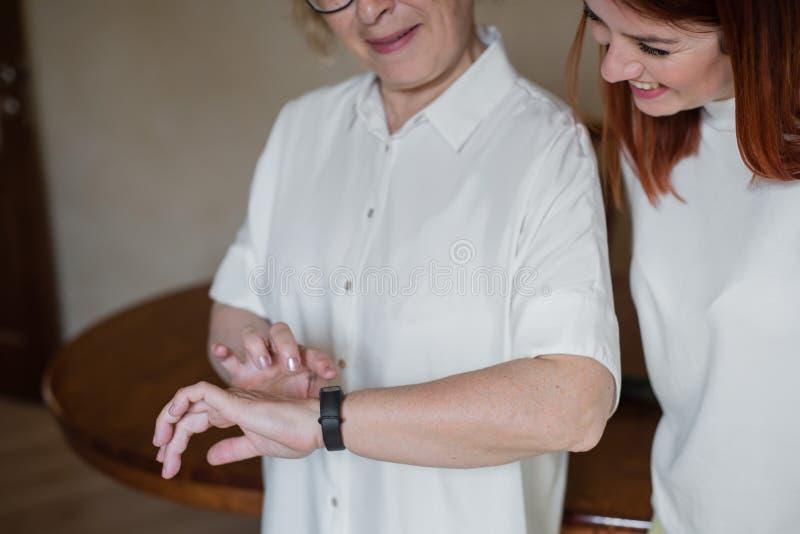 妇女帮助一个更老的母亲投入健身镯子 一个成人女儿帮助她的母亲整理设备 图库摄影
