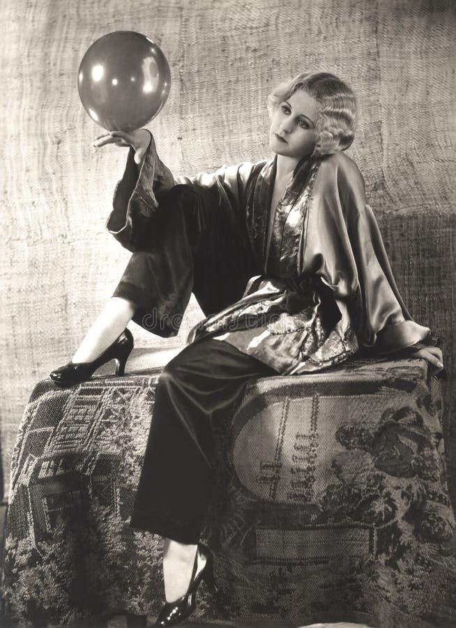妇女平衡的气球在手边 图库摄影