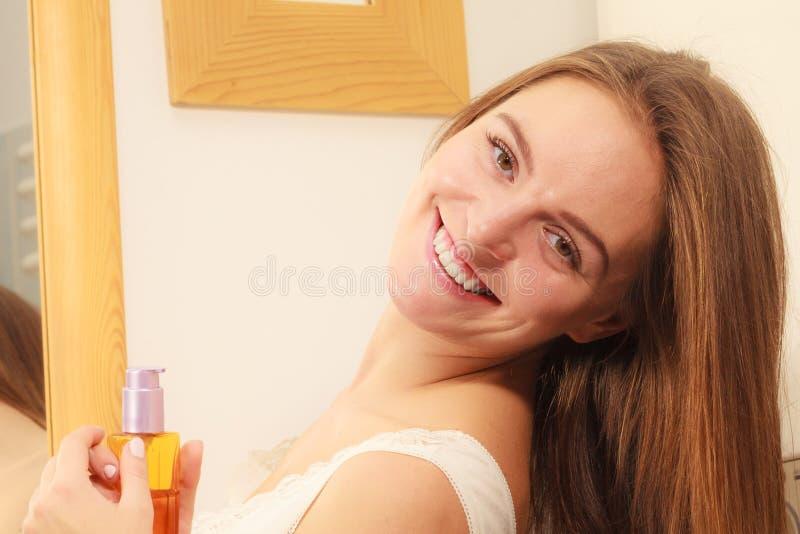 妇女应用化妆油的照料她长的头发 免版税库存图片