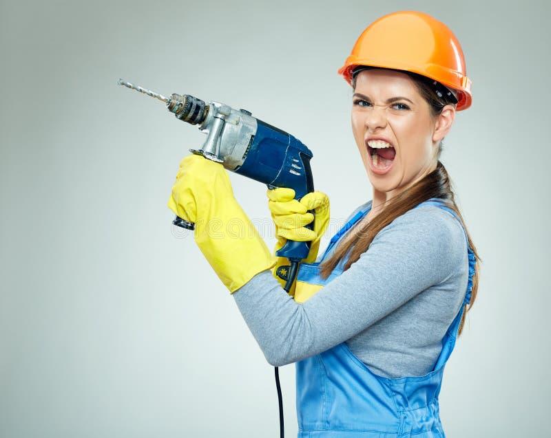 妇女建造者坚苦工作与钻子工具的 库存图片