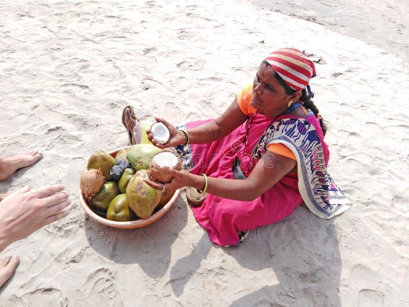 妇女开头椰子在海滩,果阿的待售 免版税库存图片