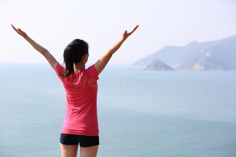妇女开放胳膊向海 免版税图库摄影
