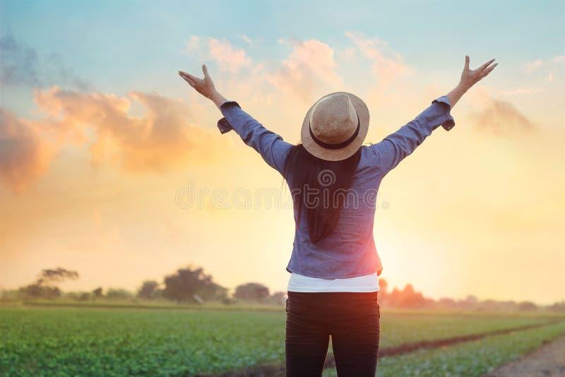 妇女开放胳膊新鲜空气在日落下的在草甸 库存照片
