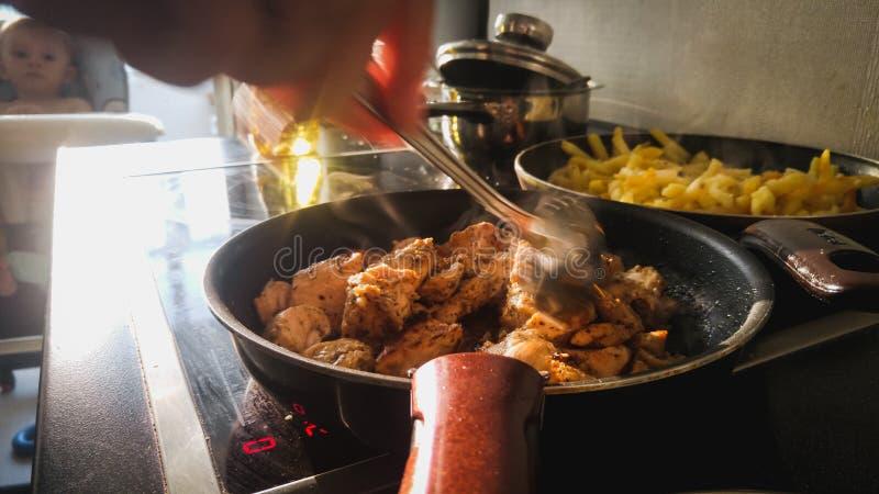 妇女引起肉的pieaces藏品叉子的特写镜头图象油煎在电火炉的平底锅 图库摄影