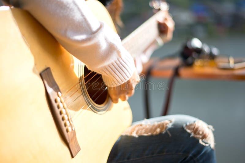 妇女弹声学吉他的` s手, 免版税库存照片
