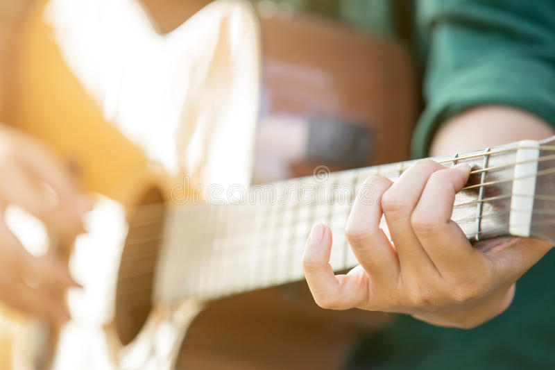 妇女弹声学吉他的` s手 免版税库存照片