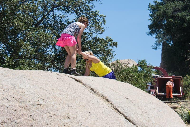 妇女徒步旅行者互相帮助在巨型冰砾顶部 配合的,女性友谊概念 库存照片