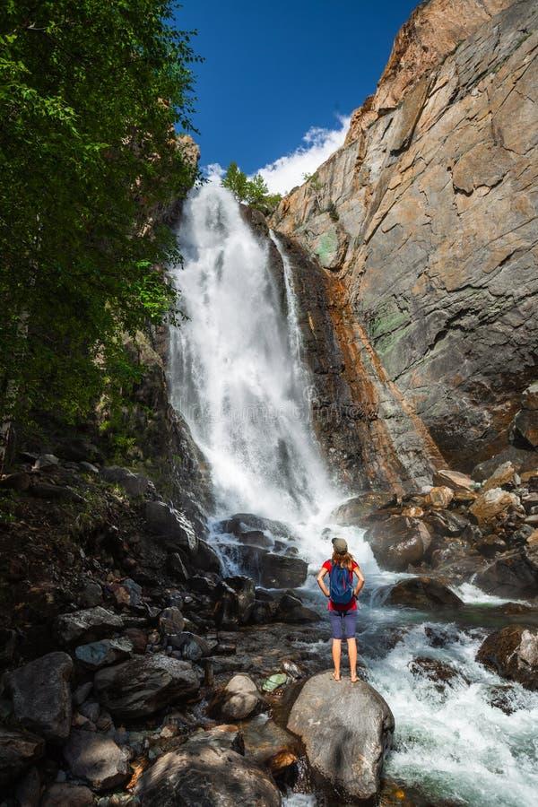 妇女徒步旅行者在岩石站立 免版税库存图片