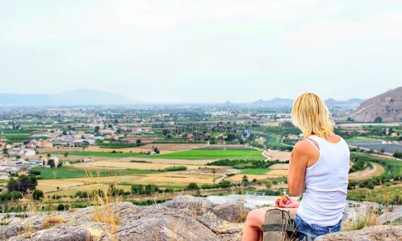 妇女徒步旅行者坐在山顶部并且放松,当吃苹果时 免版税库存图片