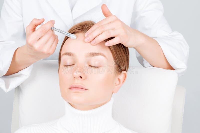 妇女得到在前额的射入 防皱治疗和更新 对妇女的面孔的脸皮举的射入 库存图片