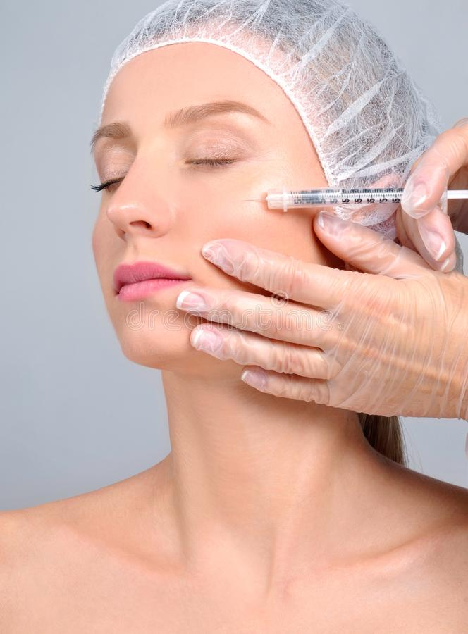 妇女得到在面颊的补白射入 防皱治疗和更新 化妆治疗和整容手术 免版税库存图片