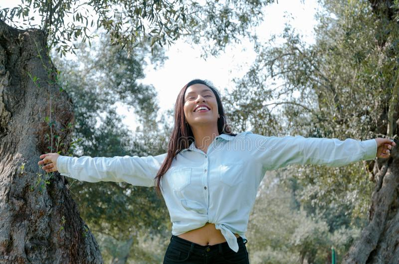妇女微笑的查寻对采取深呼吸的蓝天庆祝自由 正面人的情感面孔表示 免版税库存照片