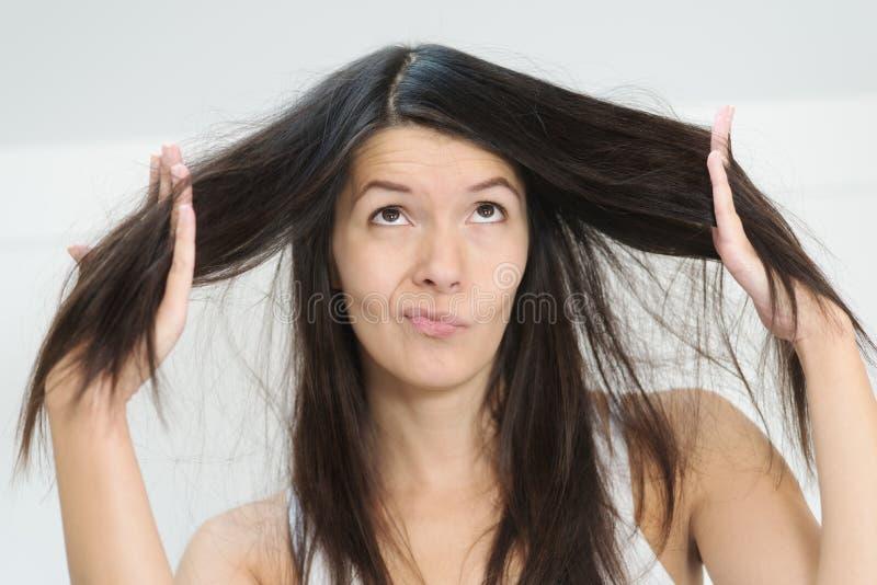 妇女怏怏不乐对于情况她长的头发 免版税图库摄影