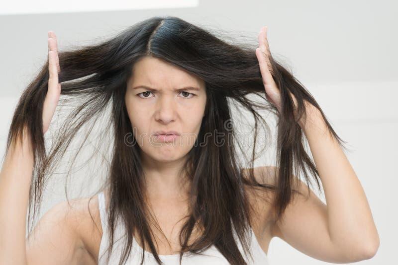 妇女怏怏不乐对于情况她长的头发 图库摄影