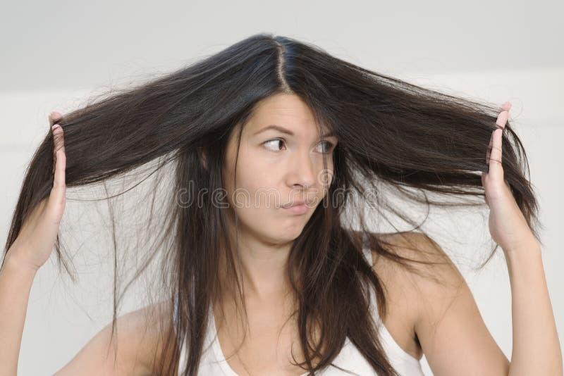 妇女怏怏不乐对于情况她长的头发 免版税库存照片