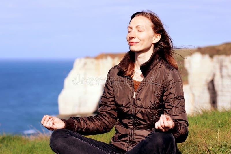 妇女思考的微笑在诺曼底峭壁顶部的瑜伽姿势在春天 库存图片