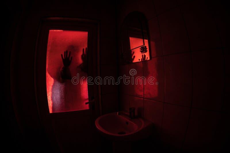 妇女恐怖剪影在窗口里 可怕巫婆万圣节概念被弄脏的剪影在卫生间里 选择聚焦 免版税图库摄影