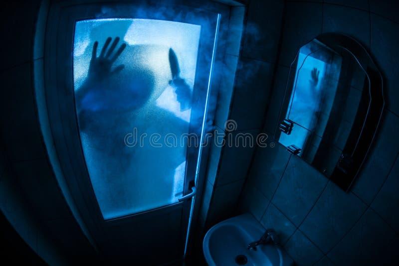 妇女恐怖剪影在窗口里 可怕巫婆万圣节概念被弄脏的剪影在卫生间里 选择聚焦 库存图片
