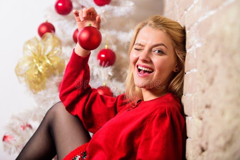 妇女愉快的举行圣诞节球装饰品 寒假概念 女孩装饰与装饰品的圣诞树 冬天 免版税库存照片