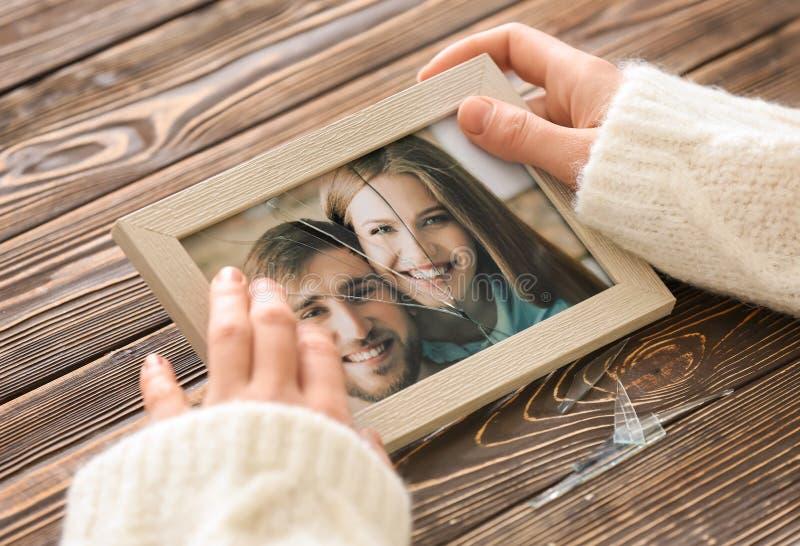 妇女愉快的夫妇藏品照片在框架的与破裂的玻璃 离婚的概念 库存图片