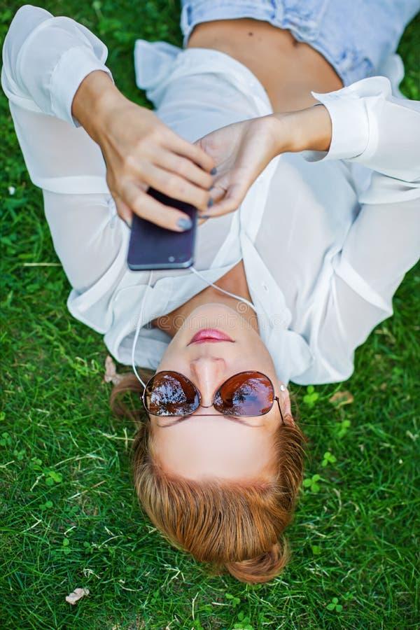 妇女感人的手机和说谎在草甸 免版税库存图片