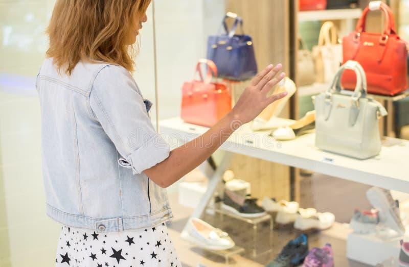 妇女感人的窗口特写镜头在袋子商店窗口前面的 库存图片