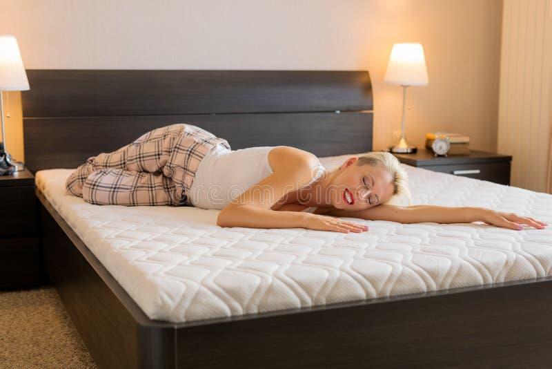 妇女感觉愉快关于她新的舒适的床垫 免版税库存图片