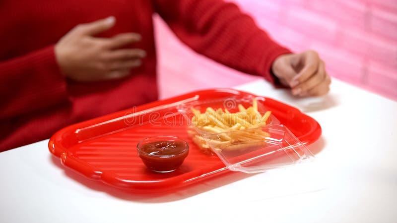 妇女感觉胃痛,薯条用在桌,酸消化不良上的番茄酱 免版税库存照片