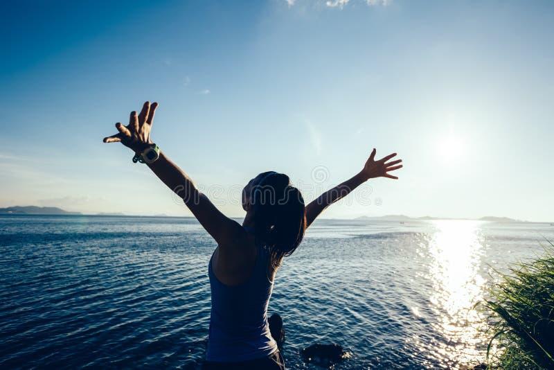 妇女慢跑者开放胳膊在日出海边 免版税库存照片