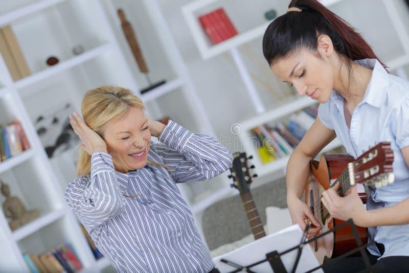 妇女懊恼在弹吉他的女儿 免版税图库摄影