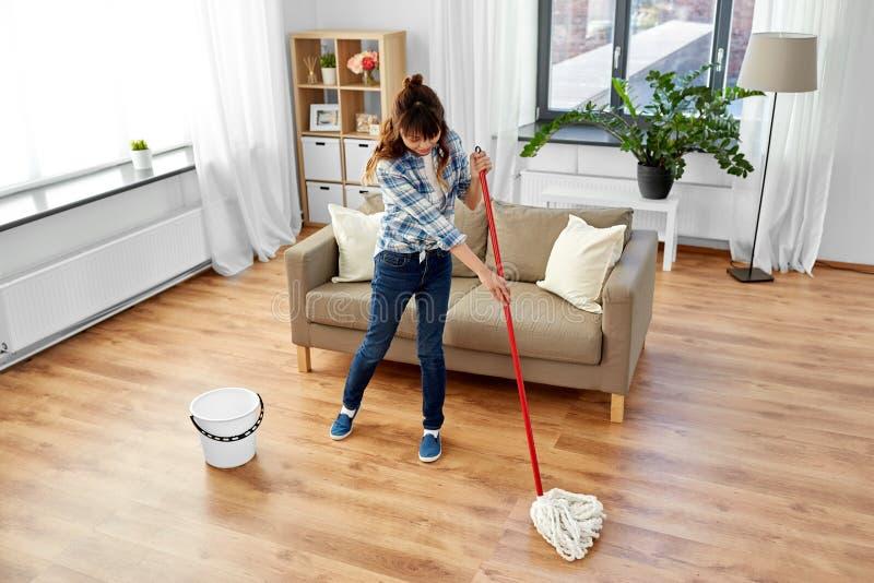 妇女或主妇有拖把清洁地板的在家 免版税库存照片