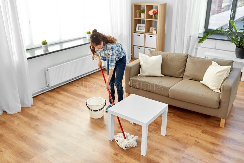妇女或主妇有拖把清洁地板的在家 库存照片