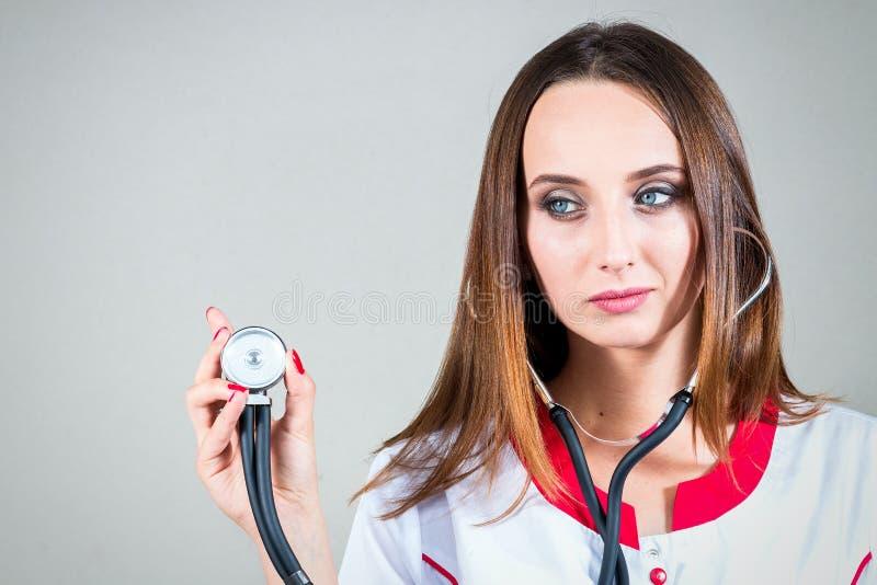 妇女或女孩护士或者医生医疗褂子的使用听诊器o 库存图片