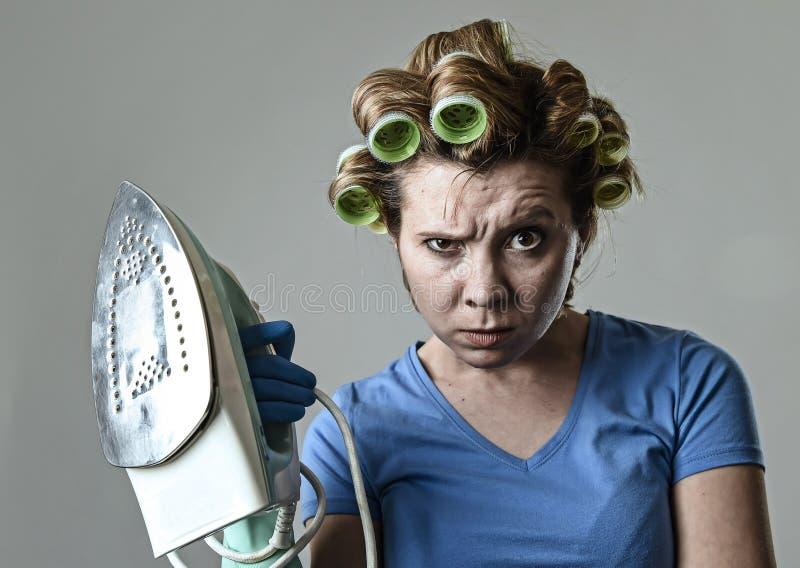 妇女或主妇沮丧哀伤的乏味和被注重的举行的铁恼怒和 免版税图库摄影