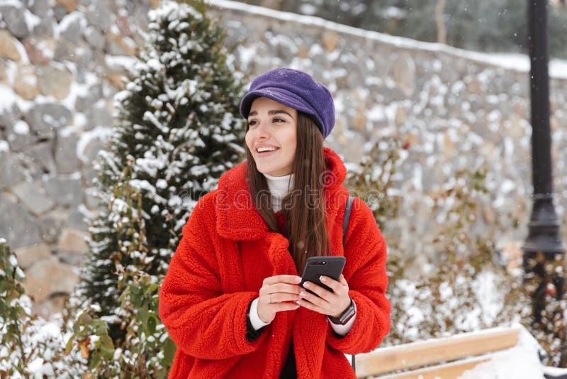 妇女户外在雪冬天使用手机的公园森林里 免版税库存照片