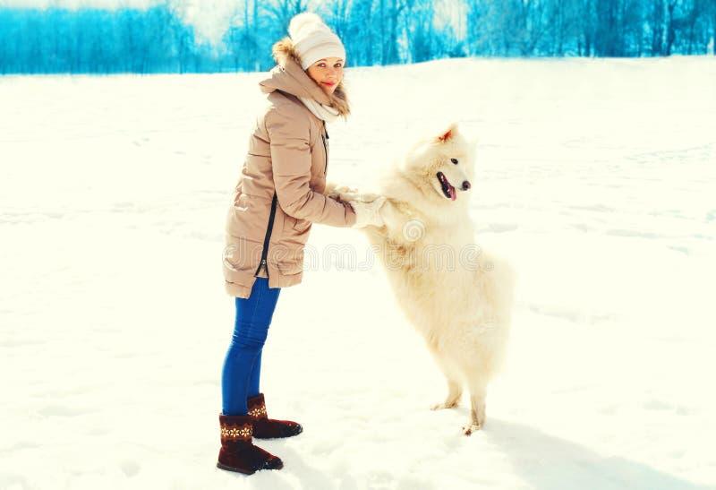 妇女所有者和白色萨莫耶特人狗在一个冬天 免版税库存照片
