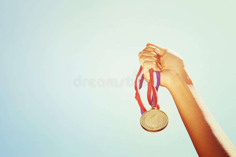 妇女手上升了,拿着金牌反对天空 奖和胜利概念 库存照片